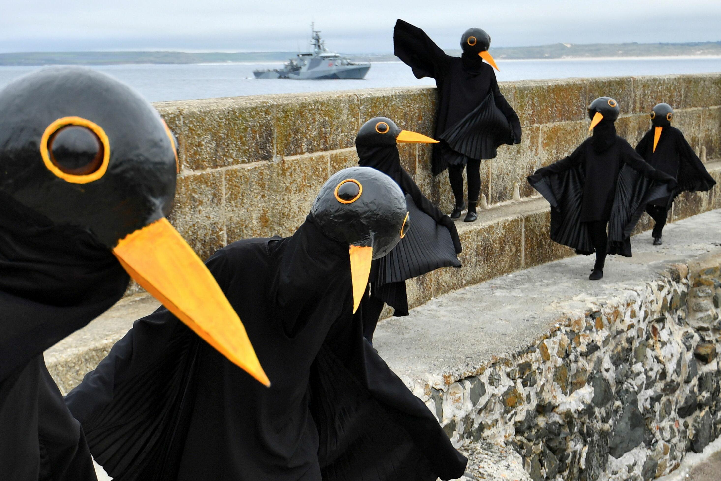 Kargo kostümü giyen bir grup, zirvenin gerçekleştirildiği esnada Cornwall sahilinde toplanarak G7 ülkelerini protesto etti.